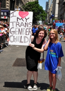 NYC:  Mother holding a sign with her child at the 2014 Gay Pride Parade on Fifth Avenue (stock pic)